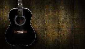Черная акустическая гитара на деревянной предпосылке Стоковые Изображения RF