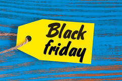 Черная бирка продаж пятницы Желтые бирки цвета на голубой деревянной предпосылке Стоковая Фотография
