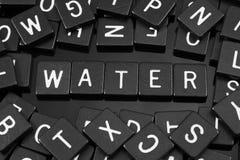 Черная буква кроет говорить черепицей слово & x22 по буквам; water& x22; Стоковая Фотография