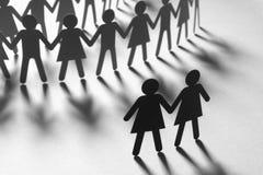Черная бумажная диаграмма женской пары перед толпой людей бумаги держа руки на белой поверхности социально стоковое фото