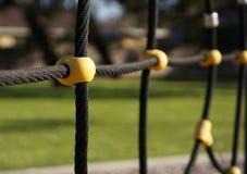 Черная веревочка и желтая крепежная деталь стоковое фото rf