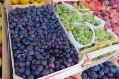 Черная виноградина и зеленая виноградина на рынке Стоковое фото RF