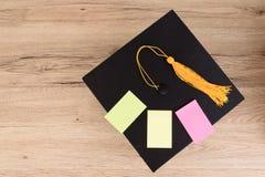 Черная градуированная крышка и желтый tassel на деревянном столе, красочном p Стоковое Изображение RF