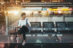 Черная девушка ждет ее самолет в крупном аэропорте стоковая фотография rf