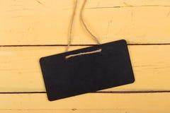 Черная доска объявлений с космосом экземпляра на деревянной предпосылке Стоковые Фотографии RF