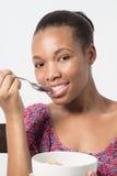 Черная женщина есть ее завтрак с ложкой Стоковые Изображения