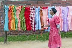 Черная женщина Зулуса с прогулками яблока за дисплеем ярко покрашенных платьев в деревне Зулуса в Zululand, Южной Африке Стоковые Изображения