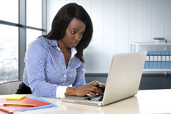 Черная женщина этничности сидя на столе компьтер-книжки компьютера печатая сконцентрированную деятельность стоковая фотография rf