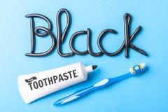 Черная зубная паста от угля для белых зубов Сформулируйте ЧЕРНОТУ от зубной пасты, трубки и зубной щетки на голубой предпосылке Стоковое Изображение
