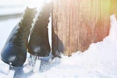 Черная диаграмма коньки лежа в снеге и ярком солнце Стоковые Фото