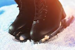 Черная диаграмма коньки лежа в снеге и ярком солнце Стоковые Фотографии RF