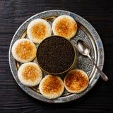 Черная икра внутри могут и здравица свежего хлеба Стоковые Изображения