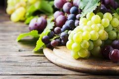 Черная и желтая виноградина на деревянном столе Стоковые Изображения