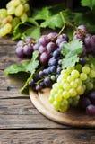 Черная и желтая виноградина на деревянном столе Стоковое фото RF