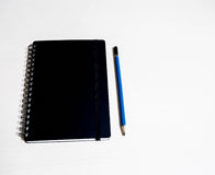 Черная книга с голубым карандашем стоковая фотография
