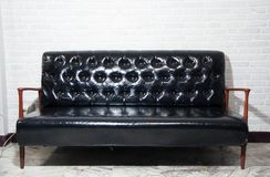 Черная кожаная софа и деревянный стул подлокотника с серой предпосылкой стоковое изображение