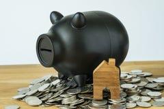 Черная копилка и деревянный миниатюрный дом на куче монеток как Стоковая Фотография RF