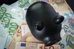 Черная копилка на куче банкнот евро как концепция сбережений Стоковые Изображения RF