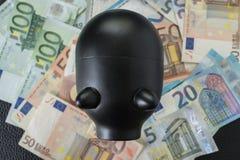 Черная копилка на куче банкнот евро как концепция сбережений Стоковая Фотография