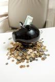 Черная копилка стоя на куче монеток на белой таблице Стоковое Фото