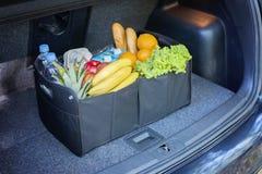Черная корзина сумки вполне продуктов в багажнике автомобиля стоковая фотография rf