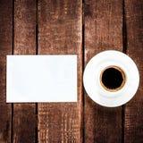 Черная кофейная чашка и пустая визитная карточка на деревянном столе бело Стоковое фото RF