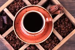 черная кофейная чашка Старая деревянная коробка с комплектом кофейных зерен, темного шоколада и циннамона Стоковое Изображение
