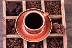 черная кофейная чашка Старая деревянная коробка с комплектом кофейных зерен, темного шоколада и циннамона Стоковая Фотография