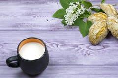 черная кружка молока Домодельные сладостные печенья Sprig и белая сирень цветут на таблице Стоковое Изображение