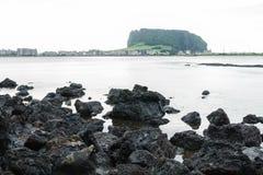 Черная лава трясет с видом на озеро к кратеру вулкана Ilchulbong, Seongsan, острову Jeju, Южной Корее Стоковая Фотография