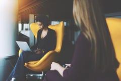 Черная молодая женщина при компьтер-книжка имея встречу с ее коллегой Стоковая Фотография