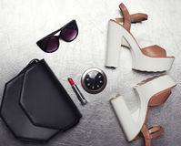 черная муфта сумки, солнечные очки, пятки ботинок, губная помада и меньшее карманное зеркало на текстурированном серебре стоковые фото