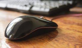 Черная мышь лазера компьютера на таблице с клавиатурой Стоковое Изображение RF