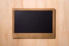 Черная доска над деревянным столом Пустая доска при деревянная стертая рамка, и подготавливает для вашего сообщения Стоковая Фотография RF