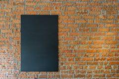 Черная доска на предпосылке кирпичной стены Стоковое Фото