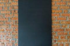 Черная доска на предпосылке кирпичной стены Стоковое Изображение RF