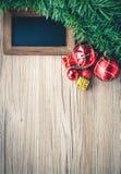 Черная доска с подарочными коробками и шарики с предпосылкой на деревянном Стоковая Фотография RF