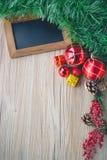 Черная доска с подарочными коробками и шарики с предпосылкой на деревянном Стоковое Фото