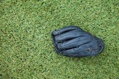 Черная перчатка на поле травы стоковая фотография rf