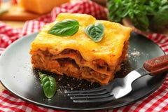 Черная плита с очень вкусной лазаньей и красной салфеткой Стоковые Фотографии RF