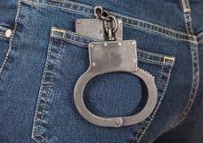 Черная полиция металла надевает наручники в карманн джинсов Стоковое фото RF