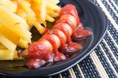 Черная плита с зажаренными сосисками и зажаренными картошками Стоковая Фотография