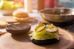 Черная плюшка бургера с салатом Стоковые Фото