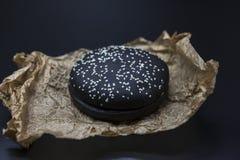 Черная плюшка для конца-вверх бургера на бумаге на темной предпосылке Стоковая Фотография