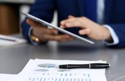 Черная ручка лежа над бумагами аналитика дела Руки бизнесмена используя планшет на предпосылке стоковое изображение