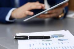 Черная ручка лежа над бумагами аналитика дела Руки бизнесмена используя планшет на предпосылке стоковое изображение rf