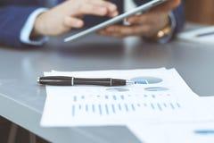 Черная ручка лежа над бумагами аналитика дела Руки бизнесмена используя планшет на предпосылке стоковые фото