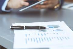 Черная ручка лежа над бумагами аналитика дела Руки бизнесмена используя планшет на предпосылке стоковая фотография rf