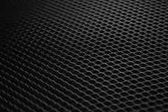 Черная сетка металла под тусклым источником света стоковые фото