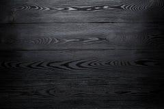 Черная сияющая деревянная абстрактная предпосылка с затмевать на краях стоковые изображения